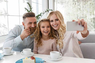 Funny young family taking selfie at restaurant stock vector
