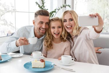 Happy young family taking selfie with tongues out at restaurant stock vector