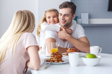 happy family having breakfast and playing on weekend morning