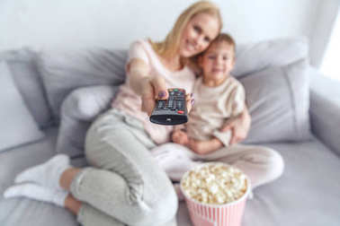 close-up shot of mother and son using remote control for tv