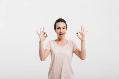 happy girl showing ok gesture with two hands isolated on white