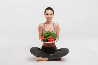 beautiful young woman sitting on floor with tray of various healthy vegetables isolated on white