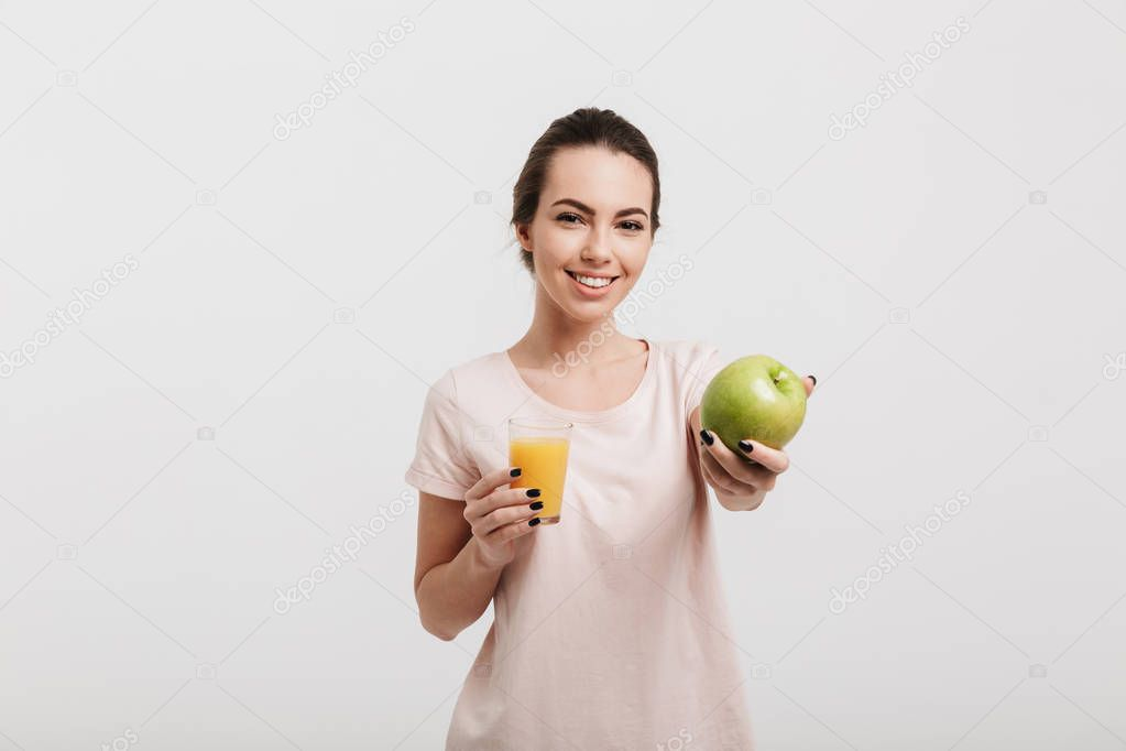smiling beautiful girl showing green apple isolated on white