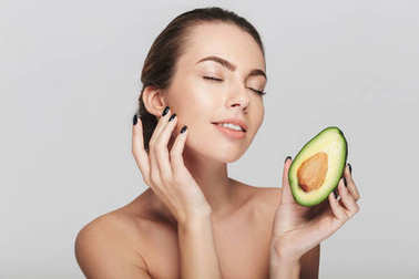 young woman with perfect skin holding half of fresh avocado isolated on white