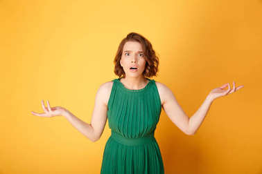 portrait of young shocked woman with outstretched arms isolated on orange