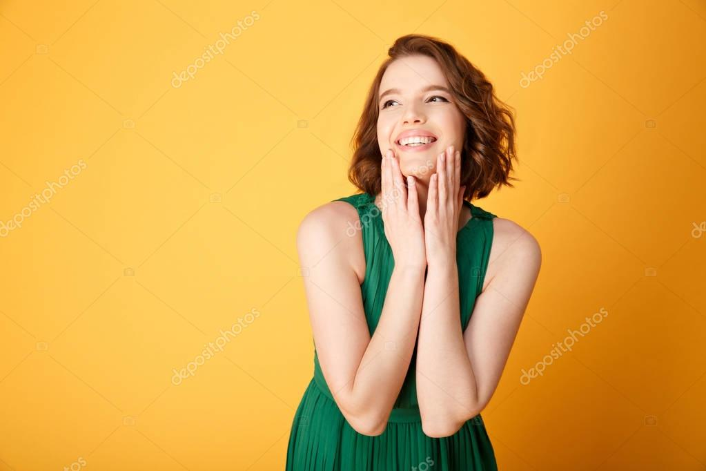 Portrait of young happy woman isolated on orange