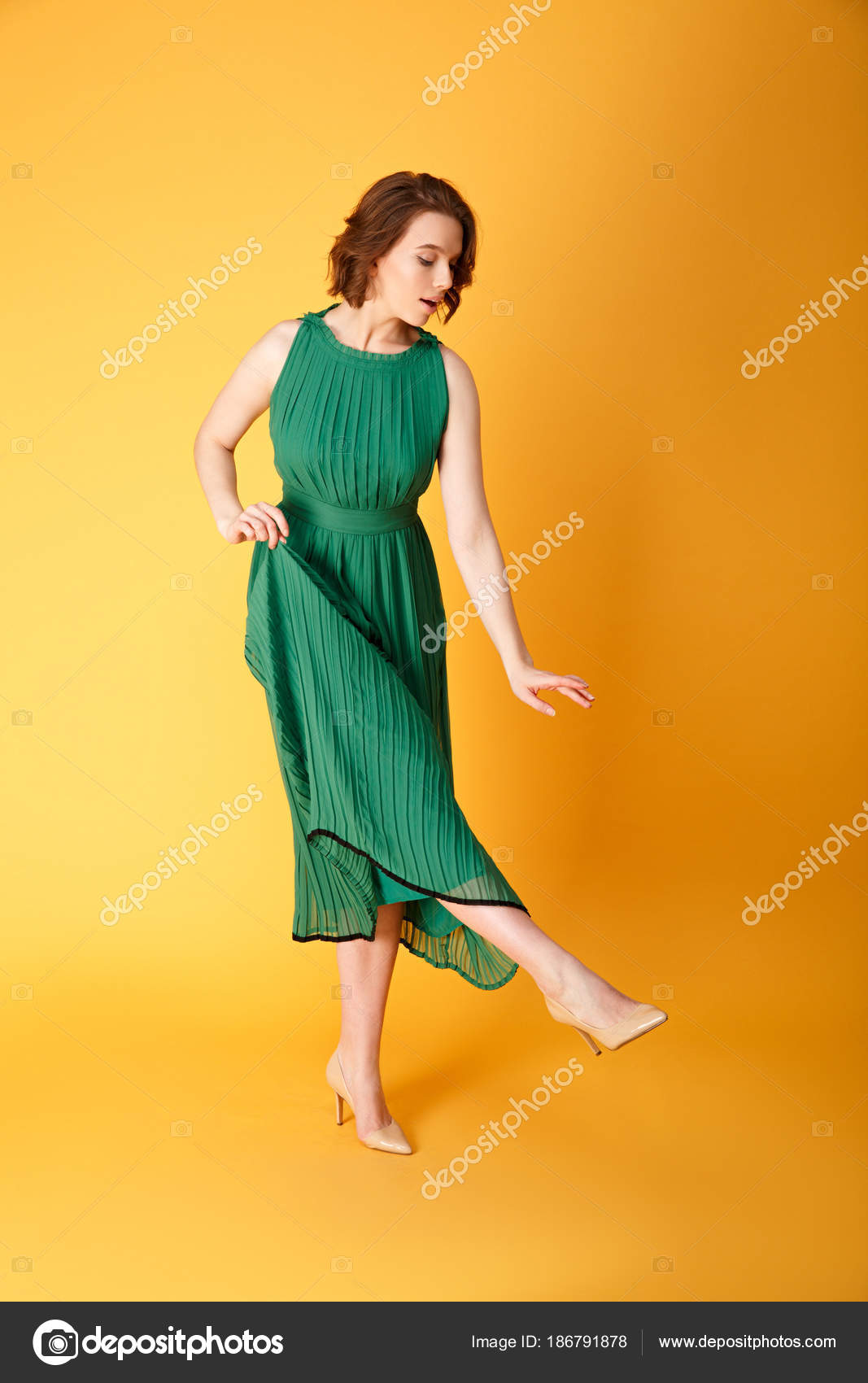 53475bd3e28c Young Beautiful Woman Green Dress Looking Shoe Isolated Orange — Stock Photo