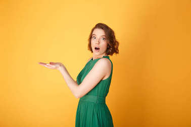 side view of shocked woman with outstretched arms looking at camera isolated on orange