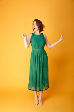young shocked woman in green dress pointing away isolated on orange