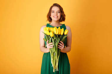 portrait of smiling woman holding bouquet of yellow tulips isolated on orange