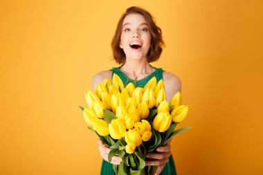 selective focus of happy woman presenting bouquet of yellow spring tulips in hands isolated on orange
