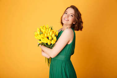 side view of beautiful woman with bouquet of yellow tulips looking at camera isolated on orange