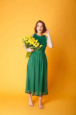 pretty young woman in green dress with bouquet of yellow tulips isolated on orange