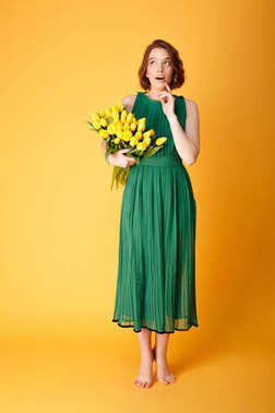 pensive young woman in green dress with bouquet of yellow tulips looking away isolated on orange