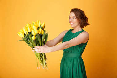 selective focus of smiling woman presenting bouquet of yellow tulips to someone isolated on orange