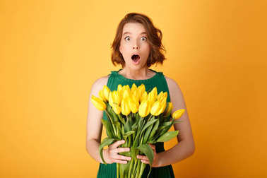 portrait of shocked woman with bouquet of yellow tulips isolated on orange