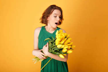 portrait of surprised woman looking at bouquet of yellow tulips isolated on orange