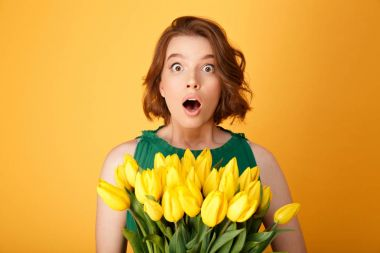 portrait of shocked woman with bouquet of yellow tulips looking at camera isolated on orange