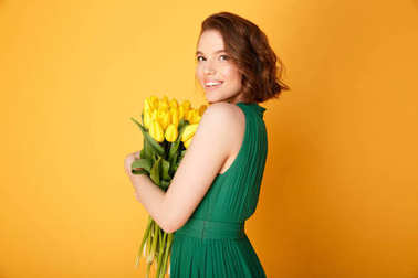 side view of cheerful woman with bouquet of yellow tulips isolated on orange
