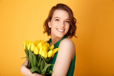 portrait of happy woman with bouquet of yellow tulips isolated on orange