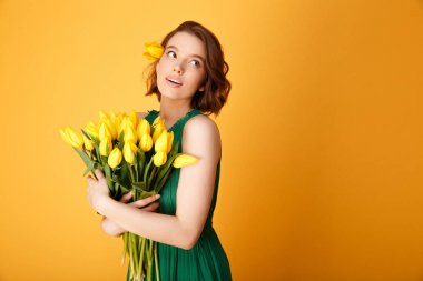 portrait of young pretty woman with bouquet of yellow tulips isolated on orange