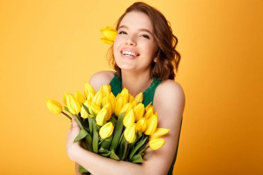 portrait of cheerful woman with bouquet of yellow tulips isolated on orange