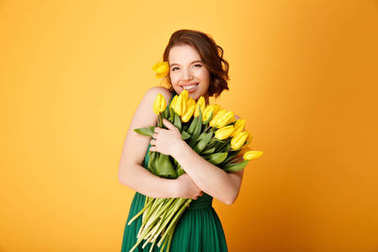 portrait of smiling woman with bouquet of yellow tulips in hands isolated on orange