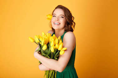 portrait of happy woman in green dress with bouquet of yellow tulips isolated on orange