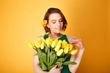 portrait of attractive woman looking at bouquet of yellow tulips in hand isolated on orange