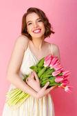 portrét usmívající se žena s kytice z růžové tulipány izolované na růžové