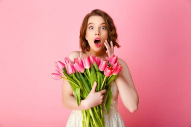 portrait of surprised woman with bouquet of spring tulips looking at camera isolated on pink