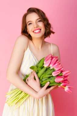 portrait of smiling woman with bouquet of pink tulips isolated on pink