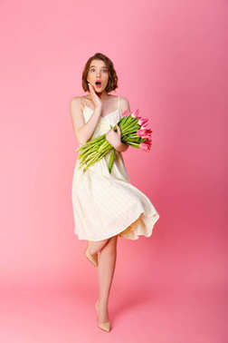 young shocked woman with bouquet of pink tulips looking at camera isolated on pink