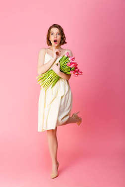 young shocked woman with bouquet of pink tulips isolated on pink