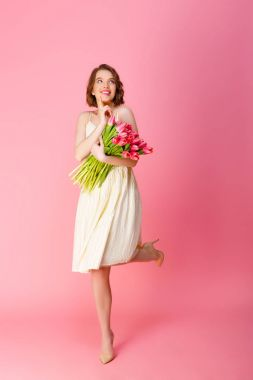 dreamy woman with bouquet of pink tulips isolated on pink