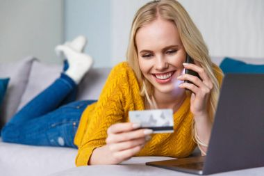 attractive happy blonde girl holding credit card and talking by smartphone while lying with laptop at home