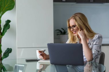 smiling young woman in eyeglasses using laptop and taking notes while working at home