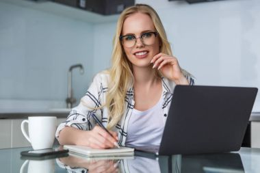 beautiful young woman in eyeglasses smiling at camera while using laptop and taking notes at home