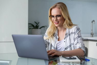 beautiful smiling young woman in eyeglasses using laptop while working at home