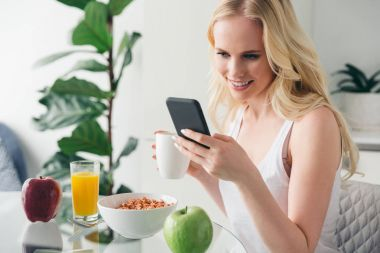 beautiful happy blonde girl using smartphone and drinking coffee at breakfast