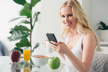 beautiful young woman using smartphone and smiling at camera during breakfast at home