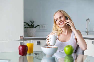 beautiful smiling young woman drinking coffee and talking by smartphone during breakfast