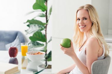 beautiful blonde girl holding apple and smiling at camera while having breakfast at home
