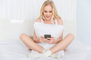 beautiful smiling young woman hugging pillow and using smartphone while sitting on bed