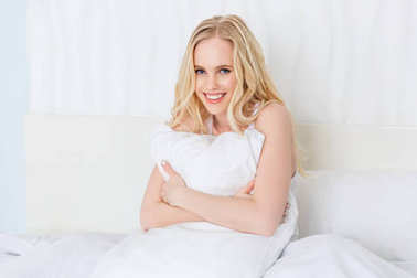 beautiful happy blonde girl hugging pillow and smiling at camera on bed