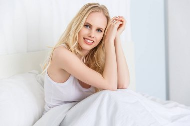 beautiful young blonde woman smiling at camera while sitting on bed at morning
