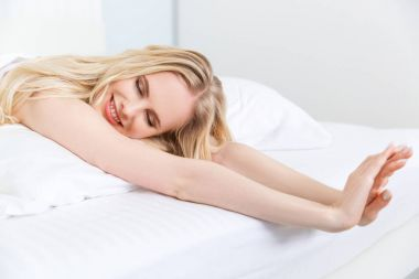 beautiful smiling blonde girl with closed eyes stretching hands on bed