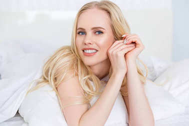 attractive blonde girl smiling at camera in bedroom