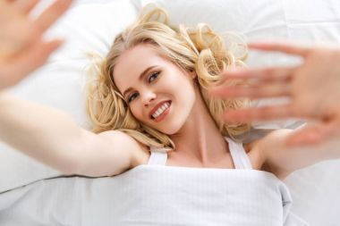 top view of beautiful young woman stretching hands and smiling at camera while lying in bed
