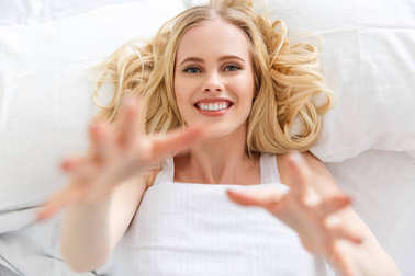 top view of attractive blonde girl smiling at camera while lying in bed